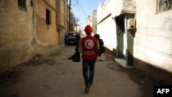 Pjesëtari i Gjysmëhënës së kuqe arabe i ndihmon një të lënduari në qytetin Douma në Siri