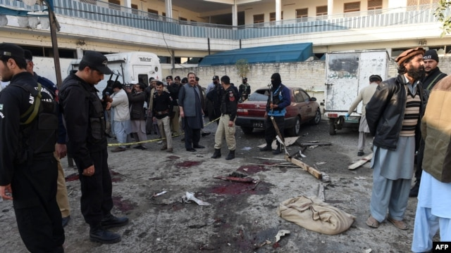 Pakistani security personnel gather evidence at the blast site of a deadly suicide attack by the TTP extremist group in the northern city of Mardan that killed at least 21 people on December 29.