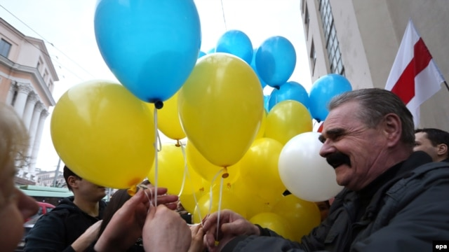 Belarusian opposition protesters share blue and yellow balloons to show their solidarity with Ukraine, during a rally marking the unofficial Freedom Day in Minsk on March 25.