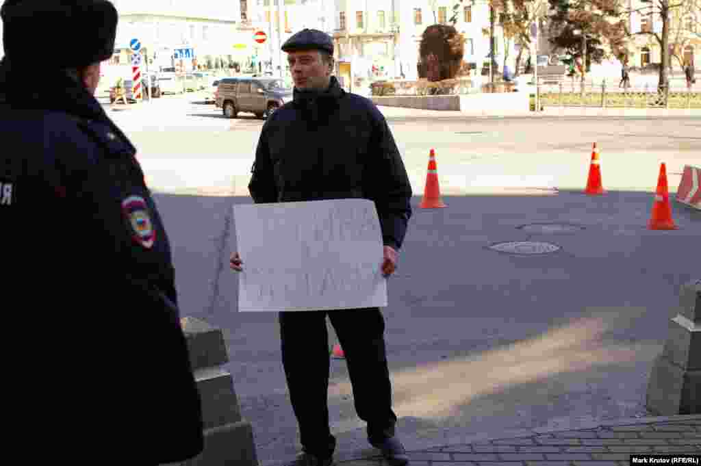 """Мужчина с плакатом """"Путина в отставку"""" внезапно появился в нескольких метрах от пикетчиков и тут же был задержан полицией. Был ли он провокатором, чья роль - нарушить правила проведения одиночных пикетов, осталось неясным"""
