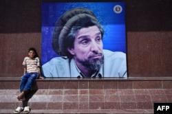 Un tînăr afgan lîngă afișul înfățișîndu-l pe Ahmad Shah Masud la Kabul