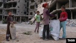 Suriyada paytaxt Dəməşqin ətrafında dağılmış qəsəbələrdən birində taxta parçaları toplayan uşaqlar. 19 oktyabr 2015