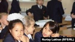 Ученики начальных классов сидят за партой в школе.