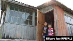 Сыновья переехавшего на север Казахстана Айдынбека Кыдырбаева на пороге дома, где временно разместилась семья. Село Краснознаменное, 23 июля 2016 года.