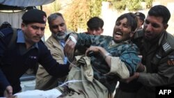 Pakistani rescuers take an injured person from the suicide bombing to the hospital in Peshawar.