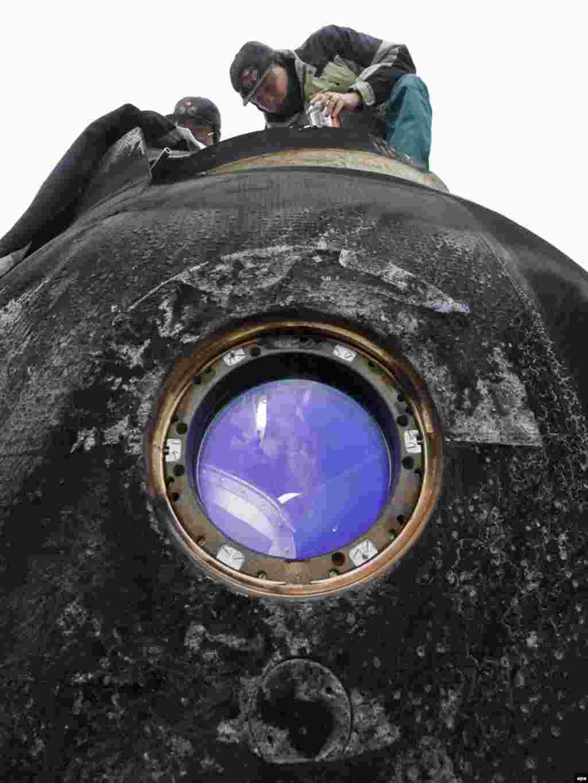 Казахстан -- Російські фахівці відкривають посадочний модуль «Союз», який повернувся з Міжнародної космічної станції - 1 грудня в посадочному модулі приземлилися бельгієць із Європейського космічного агентства Франк Де Винне, російський космонавт Роман Романенко, і канадський астронавт Роберт ТерськоPhoto by Shamil Zhumatov for epa