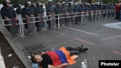 Armenia - A protester lies on the ground near riot police deployed on Marshal Bagramian Avenue, Yerevan, 26Jun2015.
