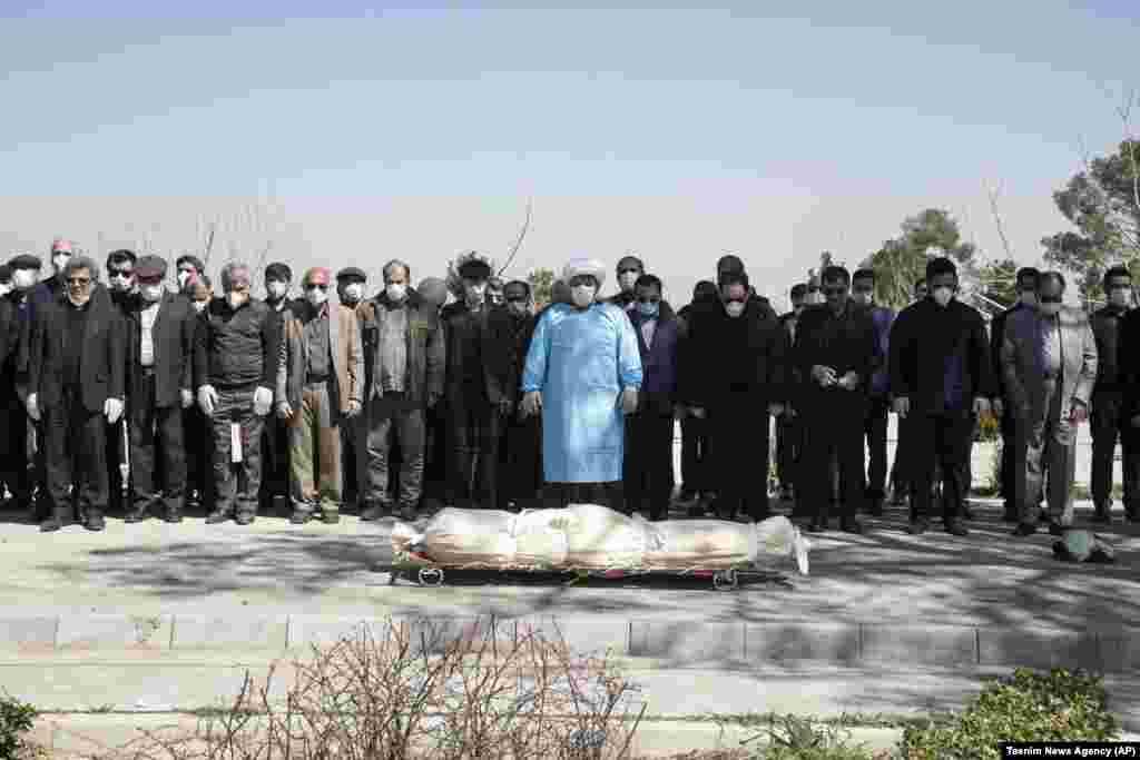 Mourners wearing face masks and gloves pray over the body of a former official in the Islamic Revolutionary Guards Corps, Farzad Tazari, who died March 9 after being infected with the new coronavirus, at the Behesht-e-Zahra cemetery just outside Tehran. (AP/Mahmood Hosseini/Tasnim News Agency)​