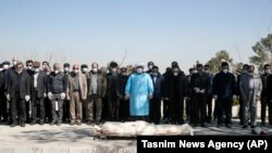 Mourners wearing face masks and gloves pray over the body of a former official in the Revolutionary Guard who died on March 9 after being infected with the new coronavirus, at the Behesht-e-Zahra cemetery just outside Tehran.