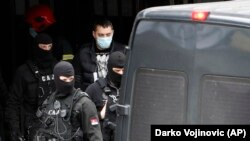 Serbian police escort detained Partizan fan leader Veljko Belivuk (center) during a raid on the Partizan stadium in Belgrade on February 4.