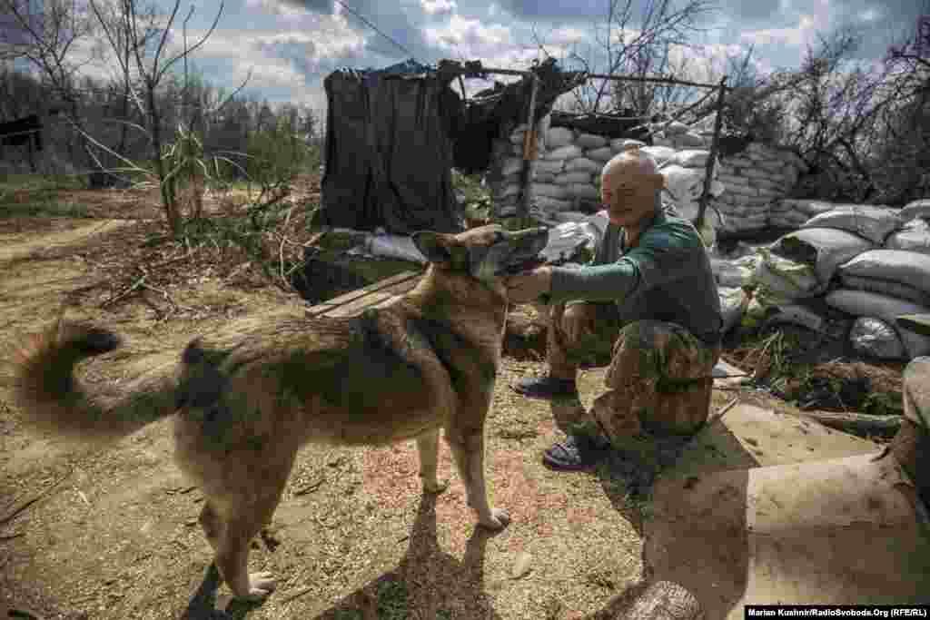 Misa bácsi megpihen kutyájával, mielőtt szolgálatra jelentkezik. A frontvonalon harcoló katonák gyakran tartanak háziállatot.