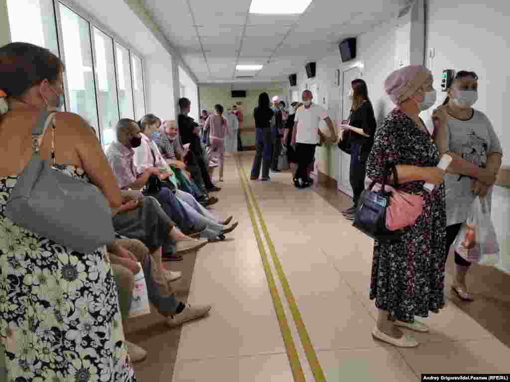 Здесь и следующие три снимка: очередь к терапевтам. Врачи принимают с двух в двух расположенных рядом кабинетах. Ещё до назначенная срока собирается общая очередь примерно из тридцати человек.