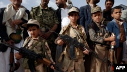 Yemeni children carrying weapons take part in a gathering organized by Shiite Huthi rebels to mobilize more fighters to battlefronts to fight pro-government forces, in the capital Sanaa, June 18, 2017