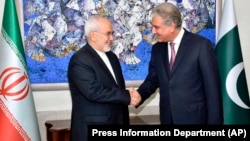 Pakistani Foreign Minister Shah Mehmood Qureshi (right) meets with Iranian counterpart Mohammad Javad Zarif in Islamabad in August 2018.