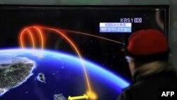 Түштүк кореялык жүргүнчү Түндүк Кореянын ракета сыноосун метронун бекетиндеги телемонитордон көрүп турат. Сеул. 12-декабрь 2012