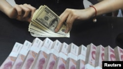 An employee counts U.S. dollars next to yuan banknotes at a bank in Hefei. (file photo)
