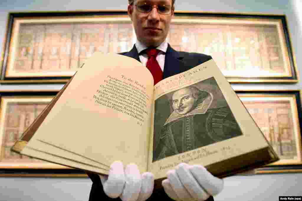 An employee of Christie's Auction House in London holds the First Folio, the first published collection of Shakespeare's plays. It is considered one of the most important books in English literature.