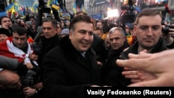 Former Georgian President Mikheil Saakashvili (center) meets pro-European integration protesters on Independence square in Kyiv on December 7.