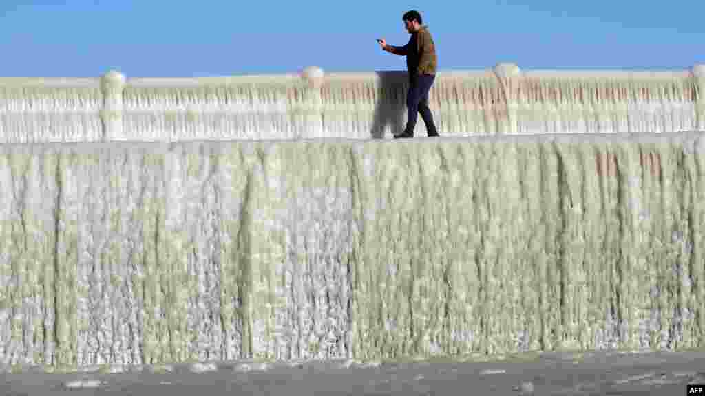 A man takes pictures of frozen seawater on a wall covered with ice in Constanta, Romania.