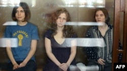 Members of the Russian feminist punk collective Pussy Riot behind a glass cage at their court hearing in Moscow. (Left to right: Nadezhda Tolokonnikova, Maria Alyokhina, and Yekaterina Samutsevich)