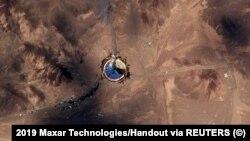 Сделанная со спутника фотография стартовой площадки космодрома имени имама Хомейни, откуда в небо поднимаются клубы дыма.