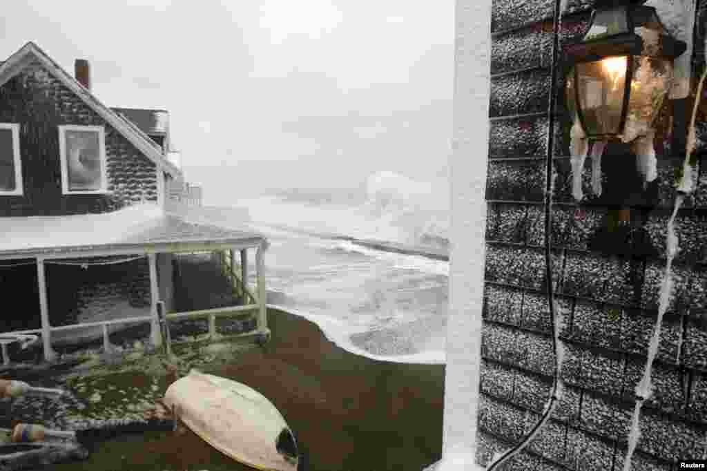 Waves crash into houses in Scituate, Massachusetts, during a storm on January 3.