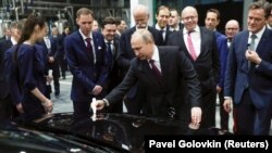 Russian President Vladimir Putin signs a car hood during the opening ceremony of a Mercedes Benz automobile assembly plant outside Moscow on April 3.