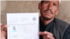 "The father of a 15-year-old girl killed in the May 8 attack on Kabul's Sayed Al-Shuhada School holds his slain daughter's ID. ""Masuma was both a son and a daughter for us,"" he said."