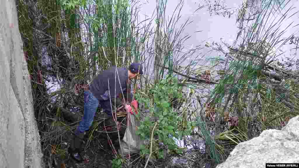 Мужчина вытаскивает из зарослей малого озера накопившийся за годы мусор.