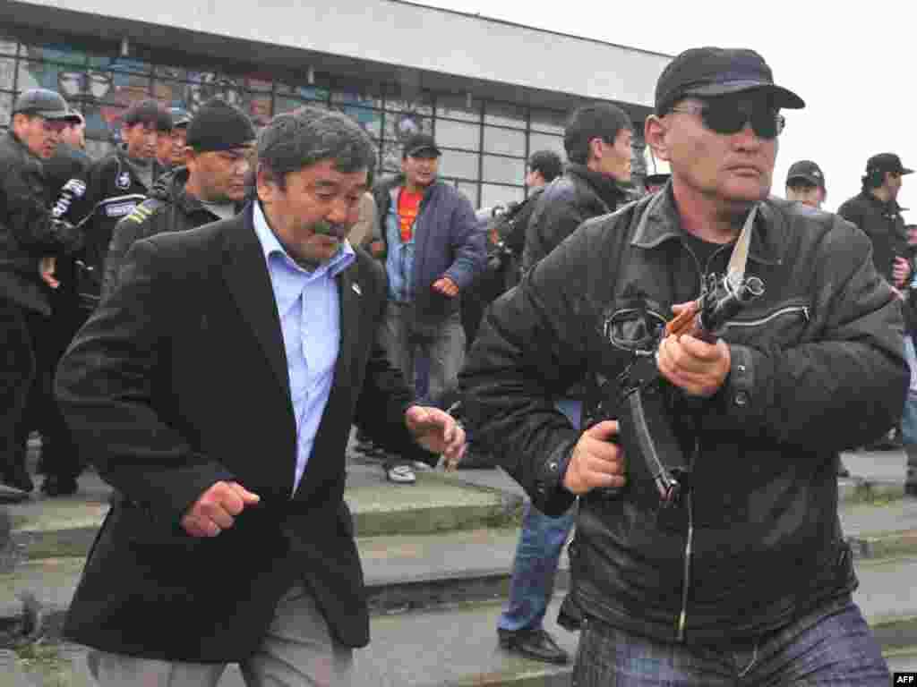 Телохранители помогают свите Бакиева покинуть митинг своих сторонников после нападения сторонников Временного правительства. Ош, 15 апреля 2010 года.
