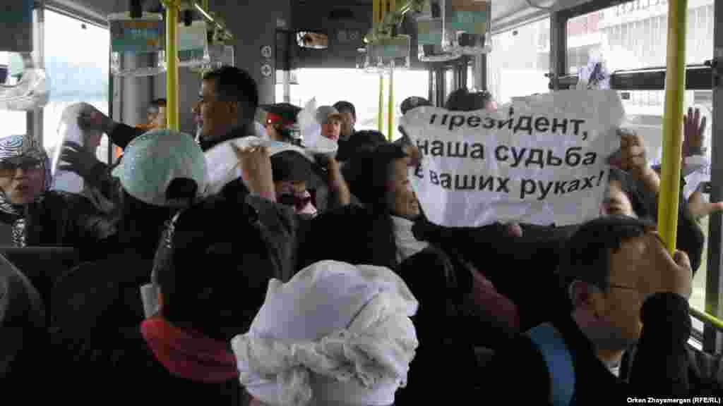 """Активист движения «ипотечников» развернул в автобусе плакат """"Президент, наша судьба в ваших руках!"""". Астана, 22 мая 2013 года."""