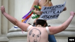 A half-naked Femen activist shows her back, where Belarusian President Alyaksandr Lukashenka is depicted, in front of the KGB headquarters in Minsk on December 19.