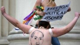 A half-naked Femen activist shows her back, where Belarusian President Alyaksandr Lukashenka is depicted, in front of the KGB headquarters in Minsk on December 19.