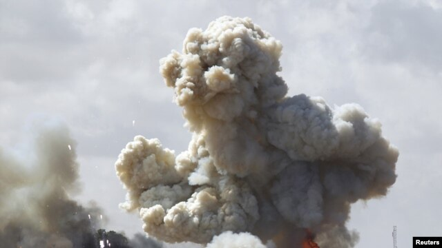 Vehicles belonging to forces loyal to Libyan leader Qaddafi explode after an air strike by coalition forces.