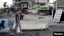 Men walk past at the site of a car bomb attack in Baghdad on August 26.