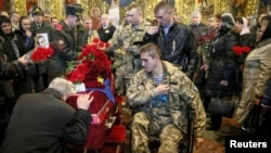 Ukrainian servicemen stand near a coffin containing the body of Ihor Branovytskiy during a funeral service in Kyiv on April 3.