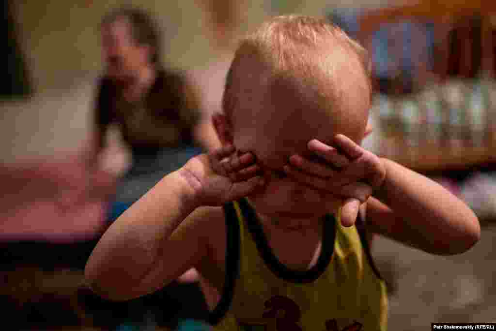 Маленький хлопчик налякано плаче від обстрілів, переховуючись у бомбосховищі в Петровському районі Донецька у серпні 2015 року. На той момент в укритті постійно проживало близько 40 місцевих жителів, зокрема 19 дітей.