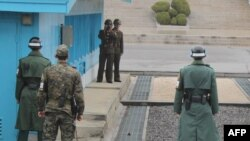 South Korea -- Korean soldiers stand guard at the tense border truce village of Panmunjom in the demilitarised zone, which splits the Korean peninsula, watched by North Korean soldiers with binoculars, 09Apr2013