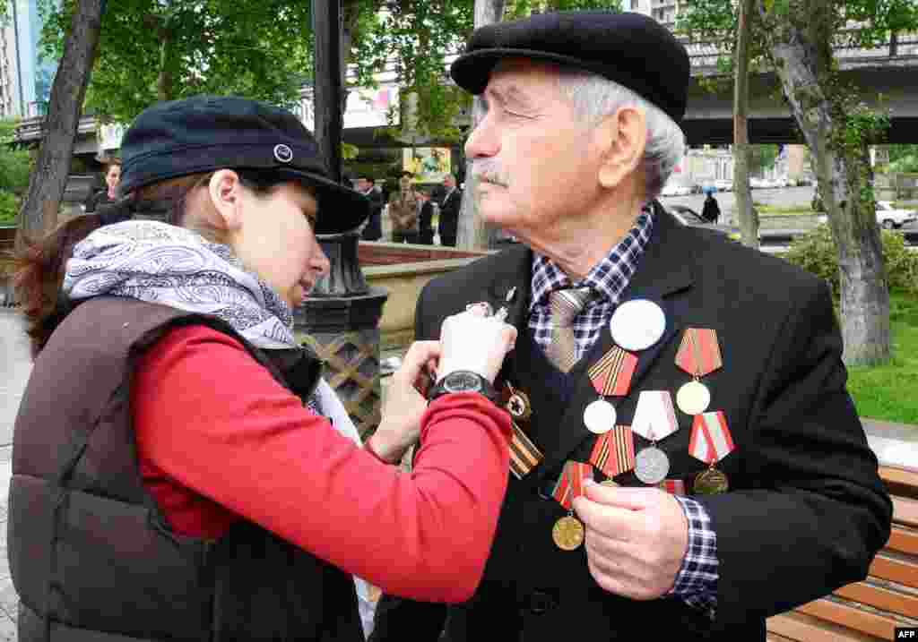 A young woman helps a WWII veteran to adjust his orange and black St. George ribbon during Victory Day celebrations in the Azerbaijani capital, Baku.