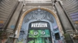 The doorway of the Capitol Summer Theater by Pisica Patrata, also known as Alexandru Ciubotariu. He is among the most well-known street artists in Romania and uses his work to draw attention to important buildings. The Capitol Summer Theater in Bucharest was built at the beginning of the 20th century and is classified as a historical monument.
