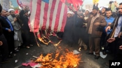 Iranians burn a U.S. flag outside the former U.S. Embassy in Tehran on November 4.