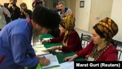 Избиратель получает бюллетень на участке в Ашгабате. 25 марта 2018 года.