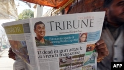 A Pakistani man reads the morning newspaper with front-page-coverage of the attack.