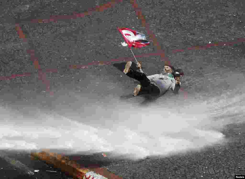 A protester holding a flag bearing an image of Mustafa Kemal Ataturk, founder of modern Turkey, falls as he is hit by a jet of water from a police water cannon during clashes on Istanbul's Taksim Square. (Reuters/Osman Orsal)