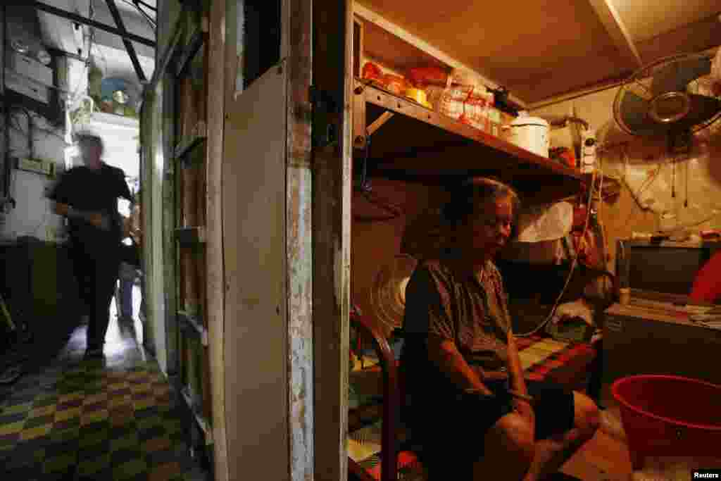 "A woman sits inside her 2.2-square-meter ""cubicle"" home in this 2009 photo."