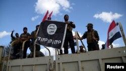 Бійці-шиїти з прапором угруповання «Ісламська держава», який вони зняли у Тікріті, 31 березня 2015 року