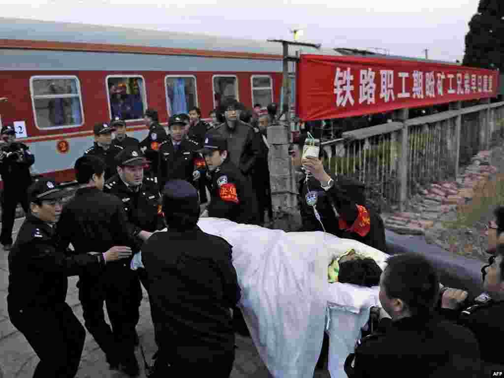 Кітайская паліцыя вывозіць шахтара, уратаванага з затопленай шахты. 115 чалавек ужо было уратавана, тысячы ратавальнікаў працягвалі пошукі яшчэ 38 чалавек.
