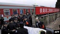 Китайские полицейские несут раненного шахтера. Провинция Шаньси.