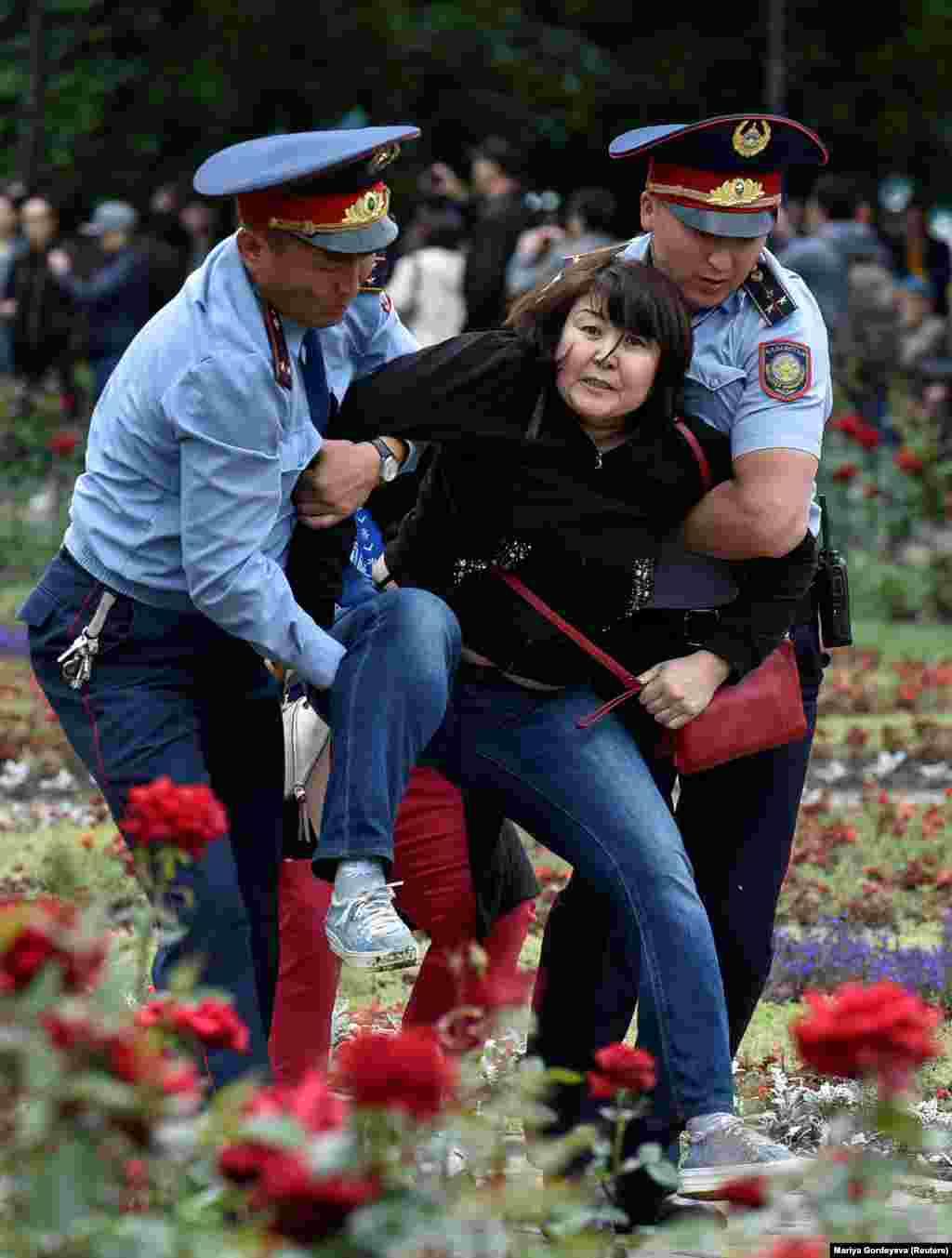 Полиция алаңға келгендердің бірін әкетіп барады. Ұсталғандар арасында Азаттық тілшісі Петр Троценко мен Vlast.kz журналисі бар. Алматы, 9 маусым 2019 жыл.