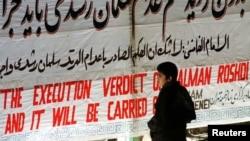 """Мальчик читает на стене Тегеранского университета плакат, на котором написано: """"Казнь Рушди будет приведена в исполнение"""""""